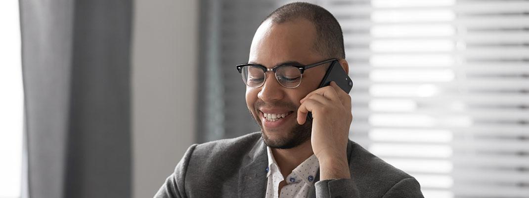 Lächelnder, brilletragender Vertriebsmitarbeiter führt ein Telefonat mit einem potentiellen Kunden.
