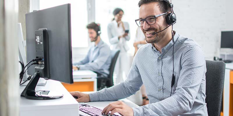 Ein lachender, junger Mann mit Headset sitzt am Computer