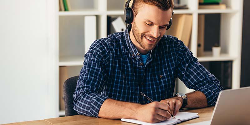 lächelnder Mann mit Kopfhörern, der Notizen macht, während er an einem Online Seminar teilnimmt